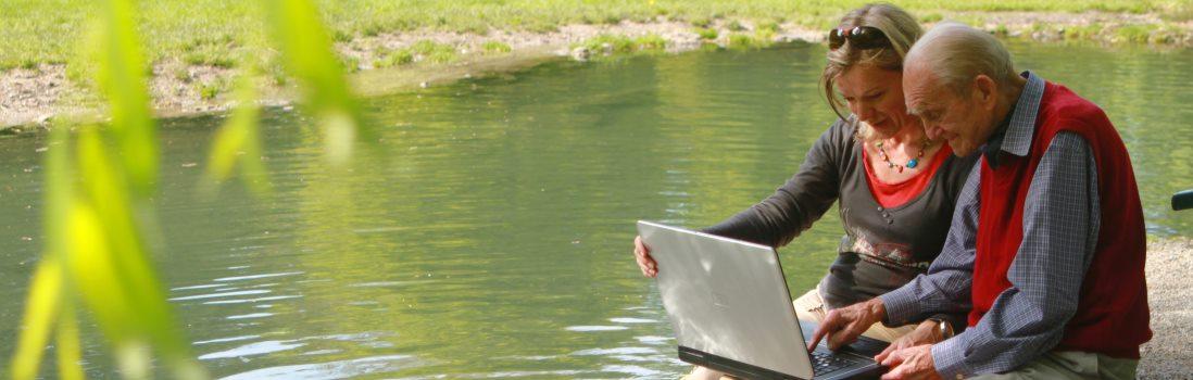 Senioren mit Laptop an einem See sitzend